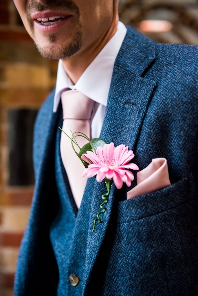 groom in a textured three piece blue suit with pink handkerchief and matching button hole