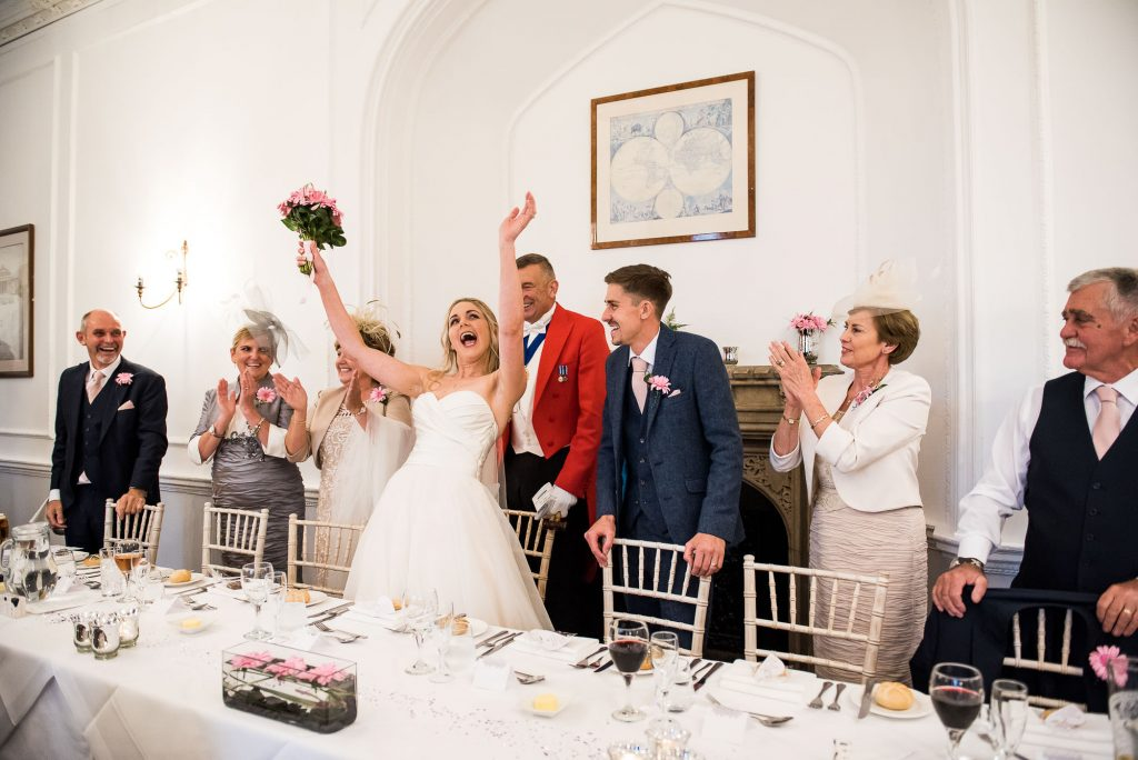 bride cheers as she is announced into the wedding breakfast