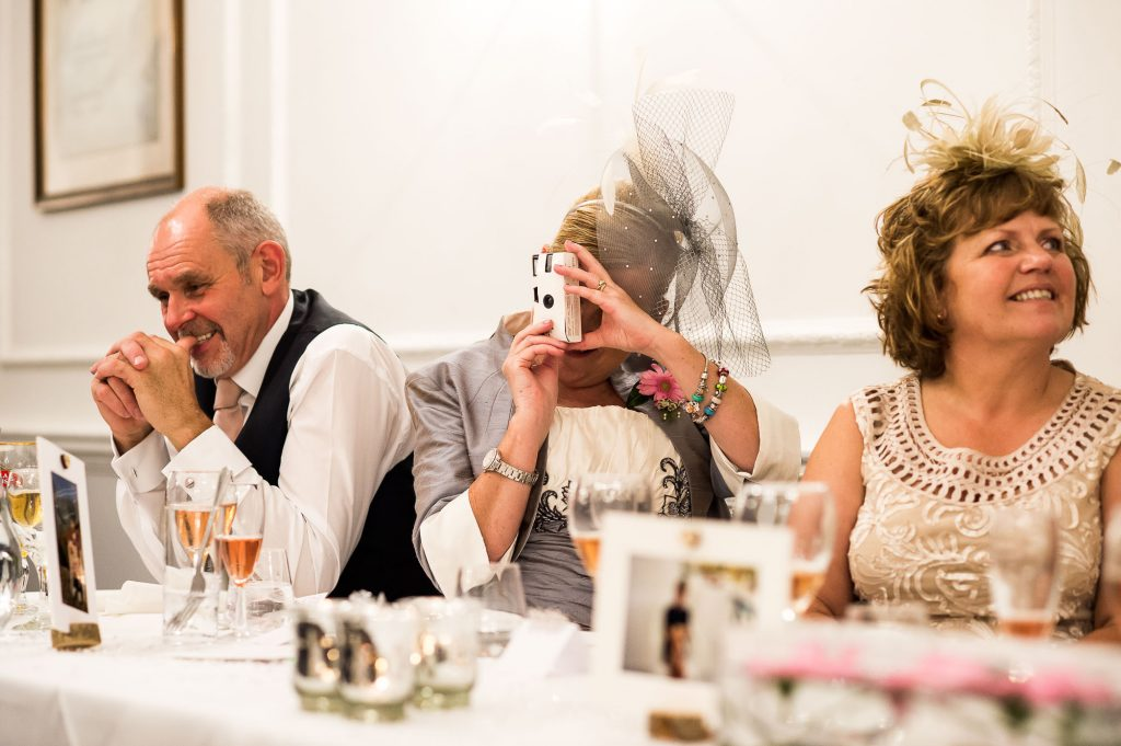 wedding guest uses disposable camera during speeches