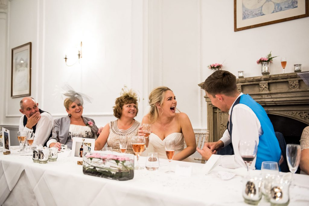 bride laughs hysterically on the top table