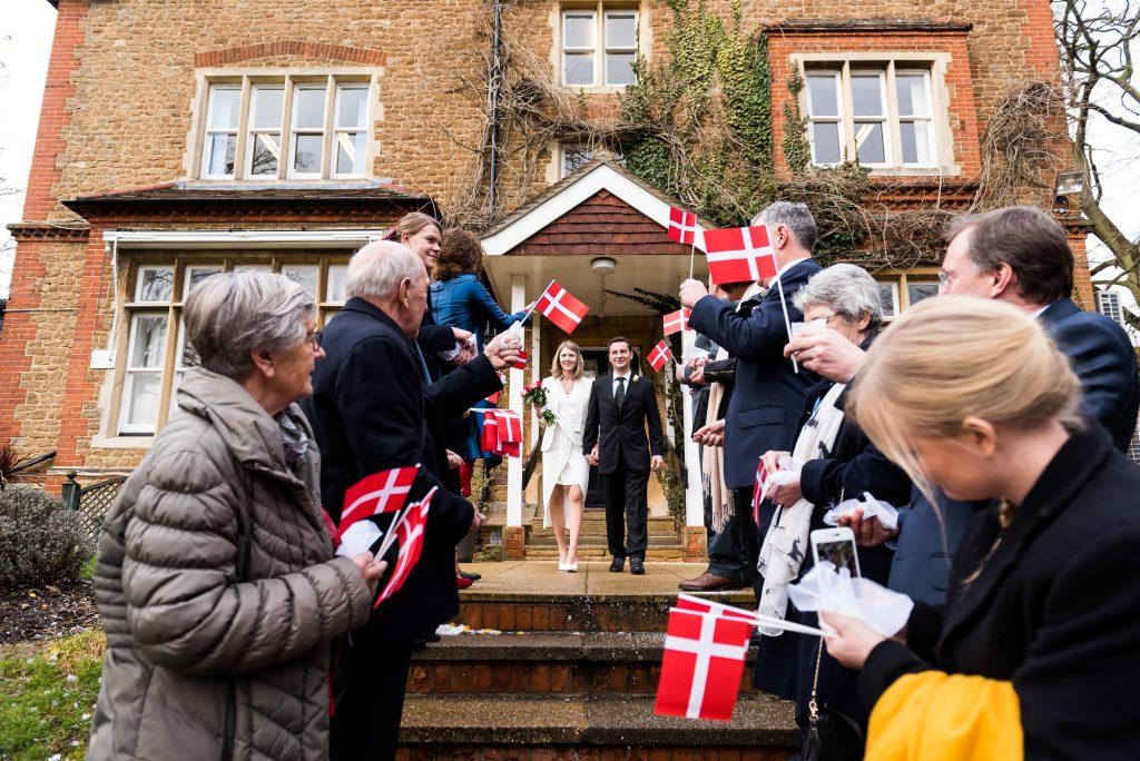 Scandinavian wedding guests wave Danish flags in confetti line Artington House wedding