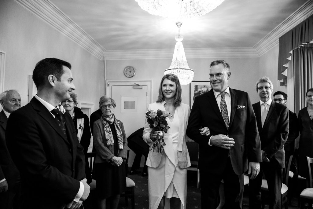 Black and white photograph of bride entering the ceremony