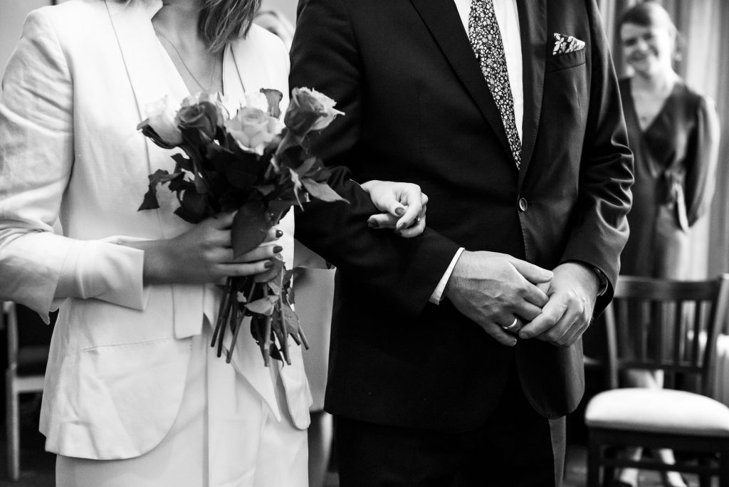 Bride holds fathers arm in intimate surrey wedding