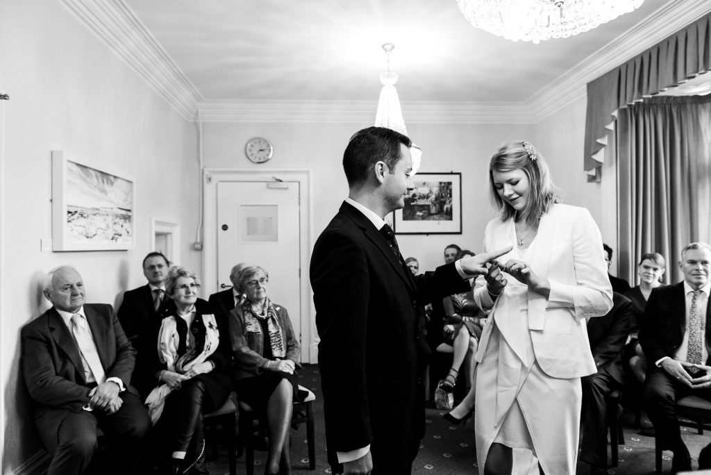 Black and white images of Groom exchanges rings with his bride