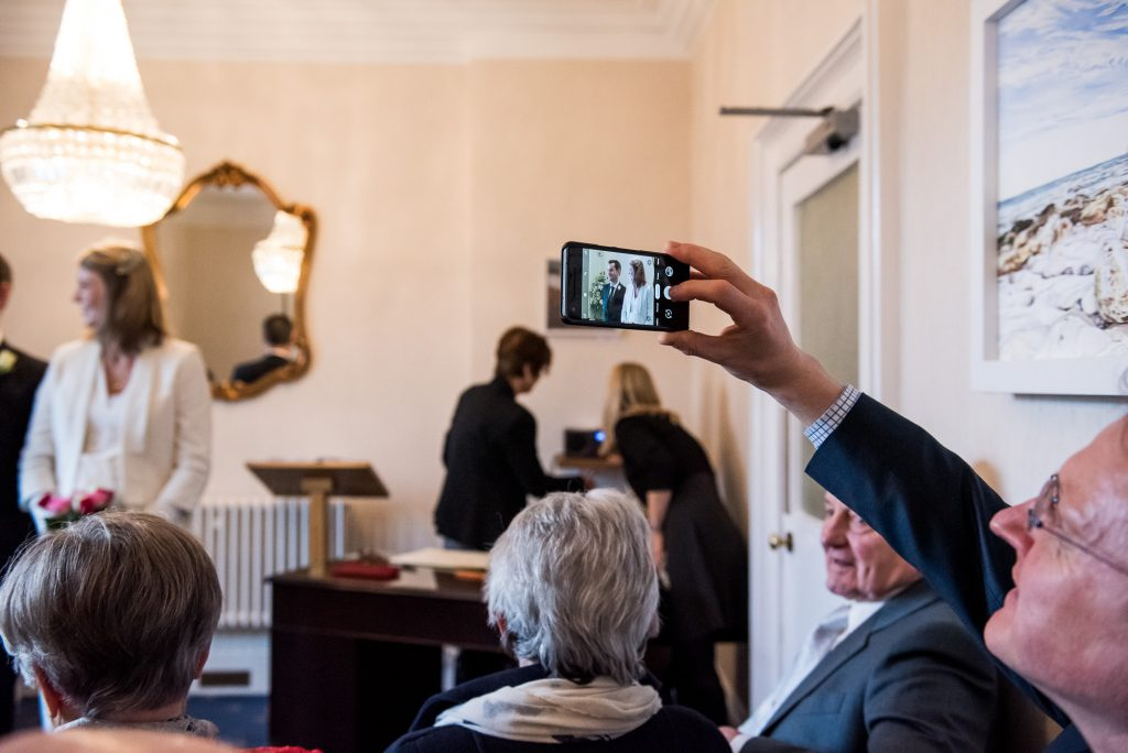 Candid documentary moment of guest photographing the bride and groom Artington House wedding