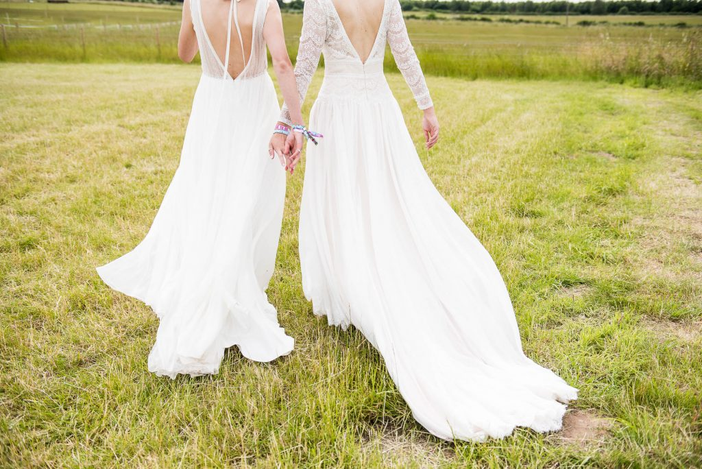 Same sex couple walk hand in had with gorgeous boho wedding dresses