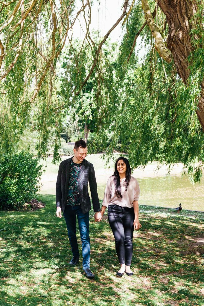 Joyous and smiling couple take a walk together under a willow tree during London engagement photography