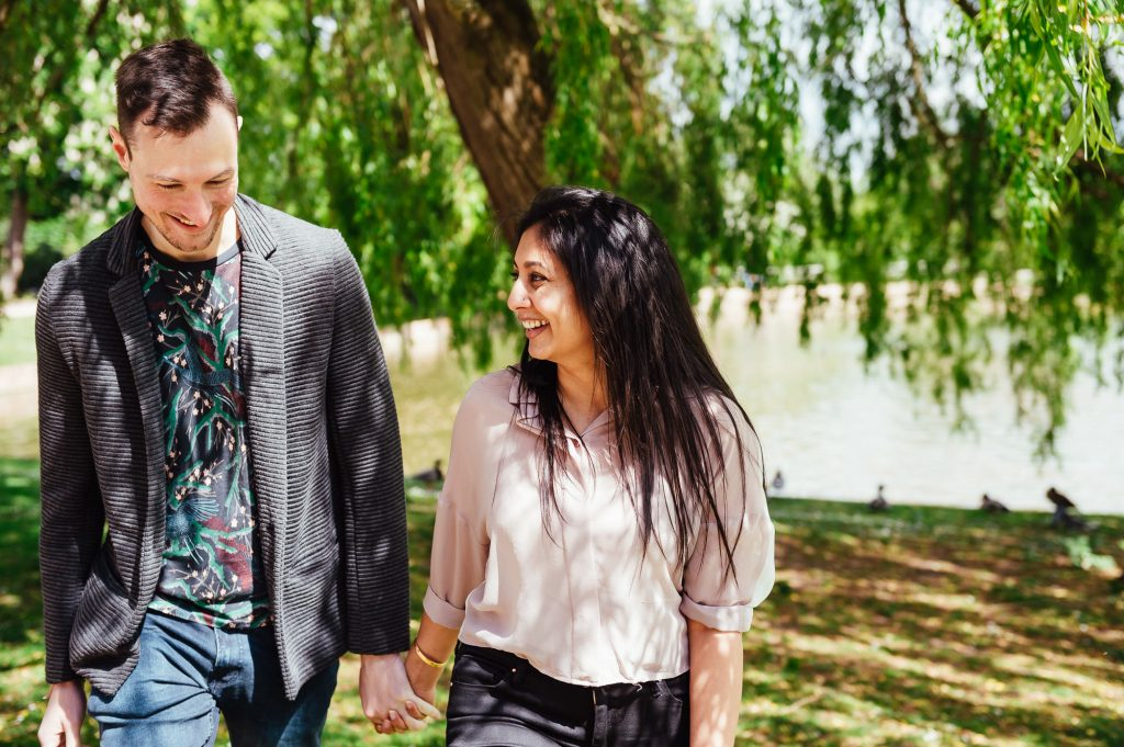 Joyous and smiling couple take a walk together under a willow tree at Forty Hall