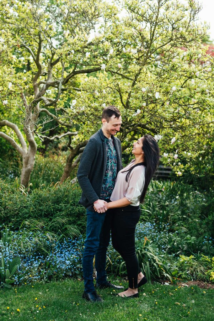 Cute couple smile at each other on Forty Hall engagement shoot, London engagement photography