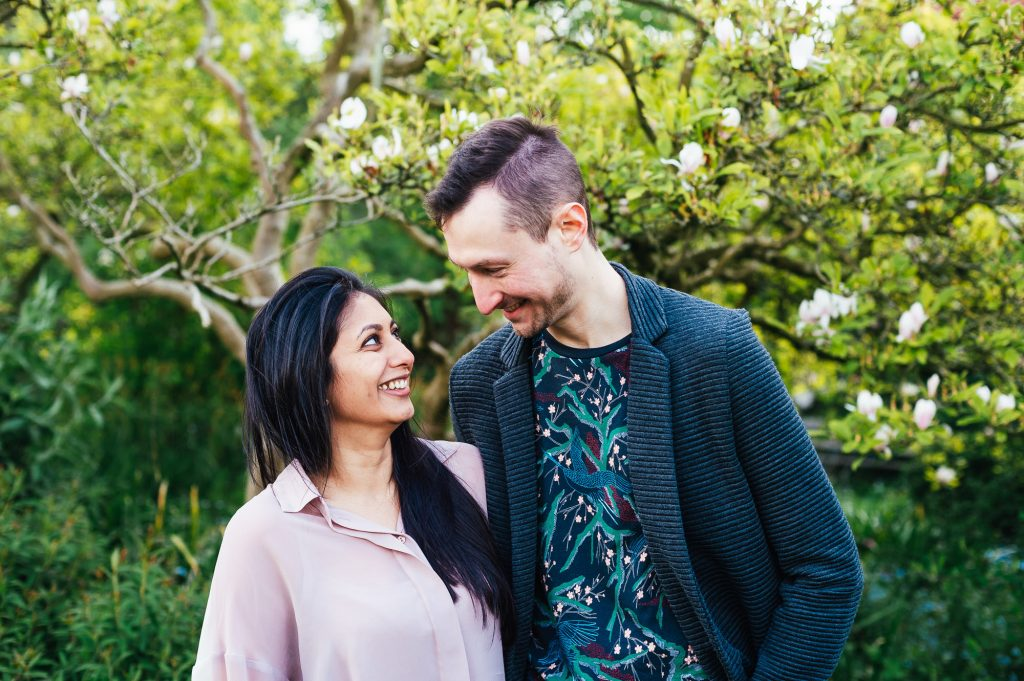 Cute couple smile at each other on Forty Hall engagement shoot