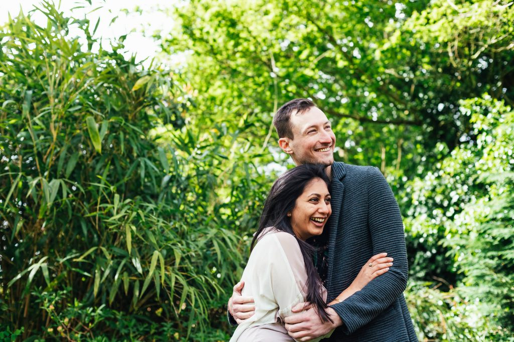 Couple hold each other in a comfortable and romantic embrace surrounded by green foliage