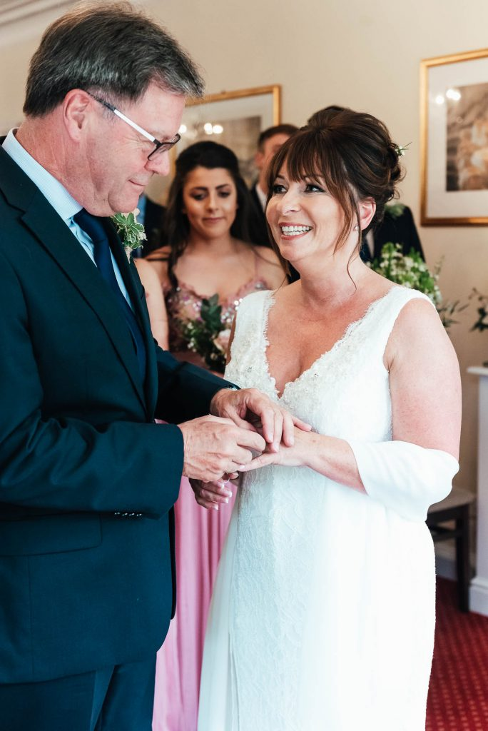 couple exchange rings during weybridge registry office ceremony