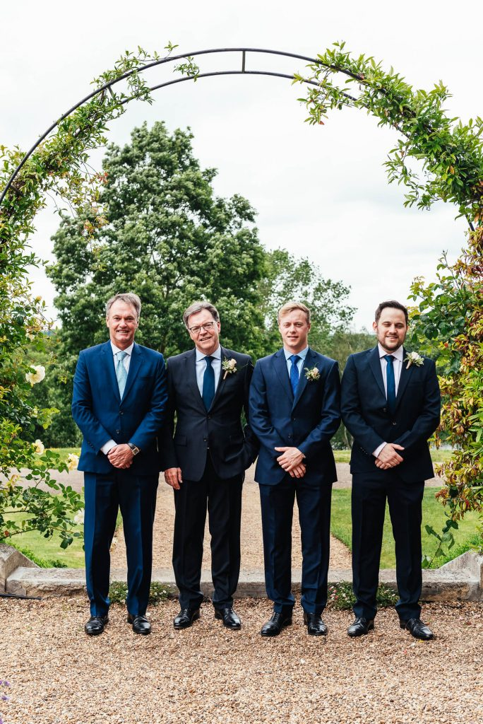Stylish groomsmen in the gardens of Oatlands Park