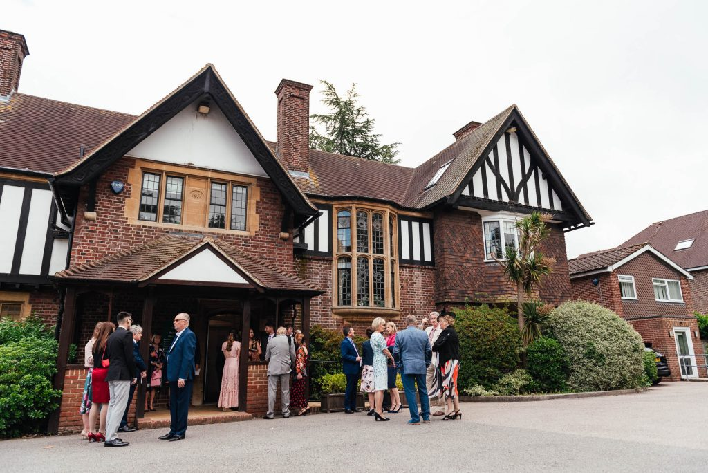 Guests wait for bride and groom outside Weybridge Registry Office