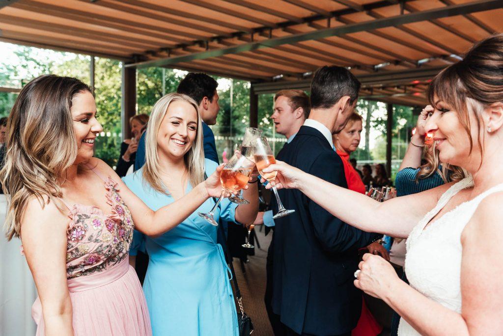 Guests cheers at Oatlands Park wedding reception