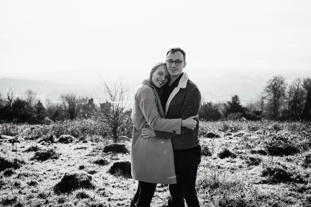 Black and white image of couple hugging in Surrey countryside