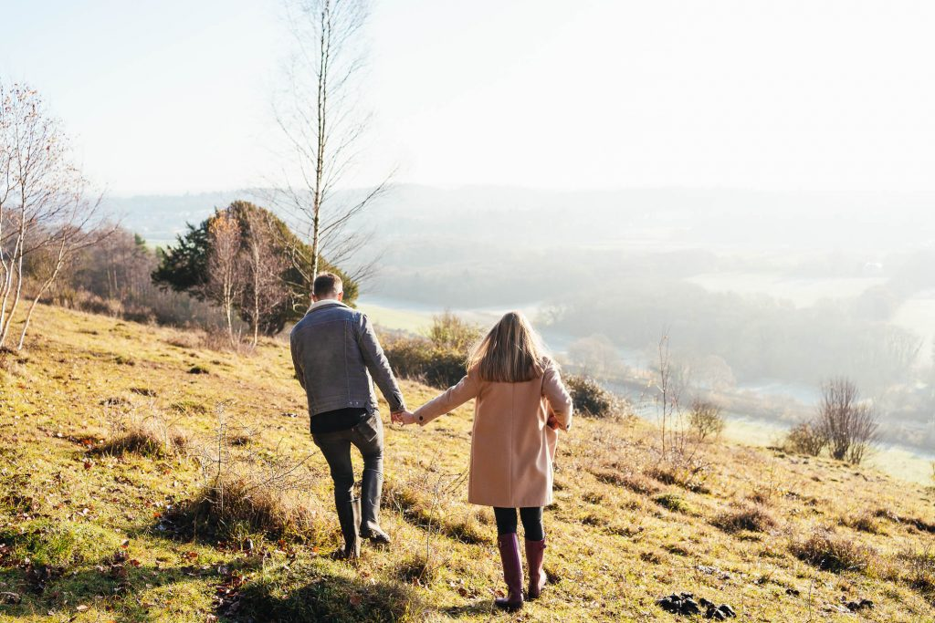 Couple walk hand in hand along the Surrey countryside