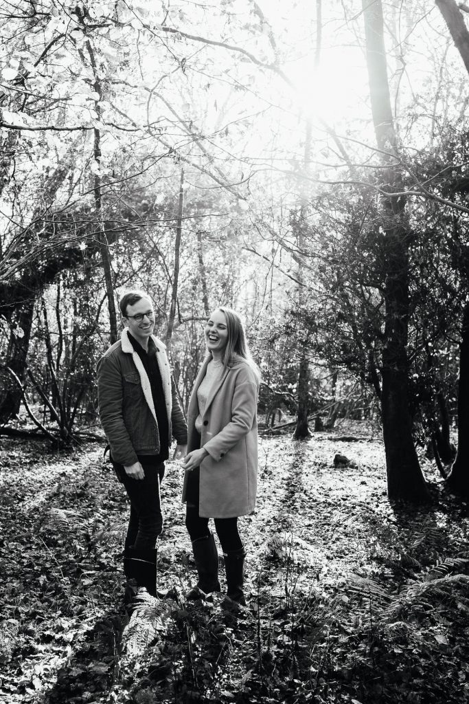 Black and White image of couple standing in woodland