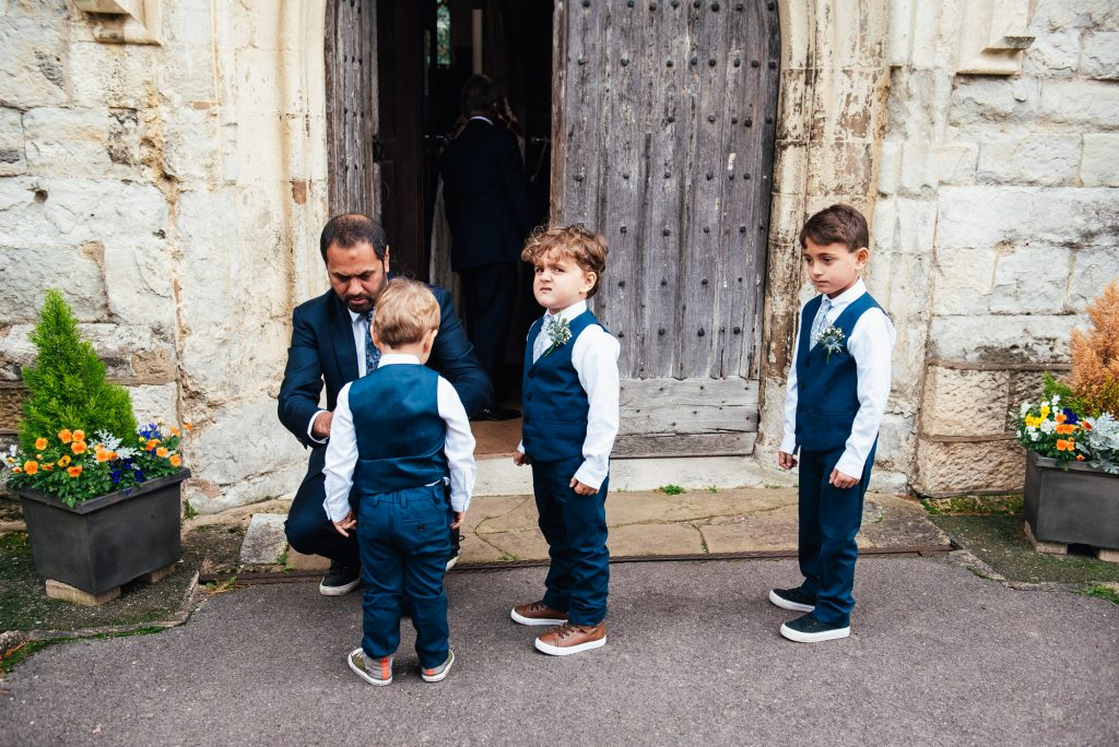Page boys dressed in matching navy blue suits wait outside church