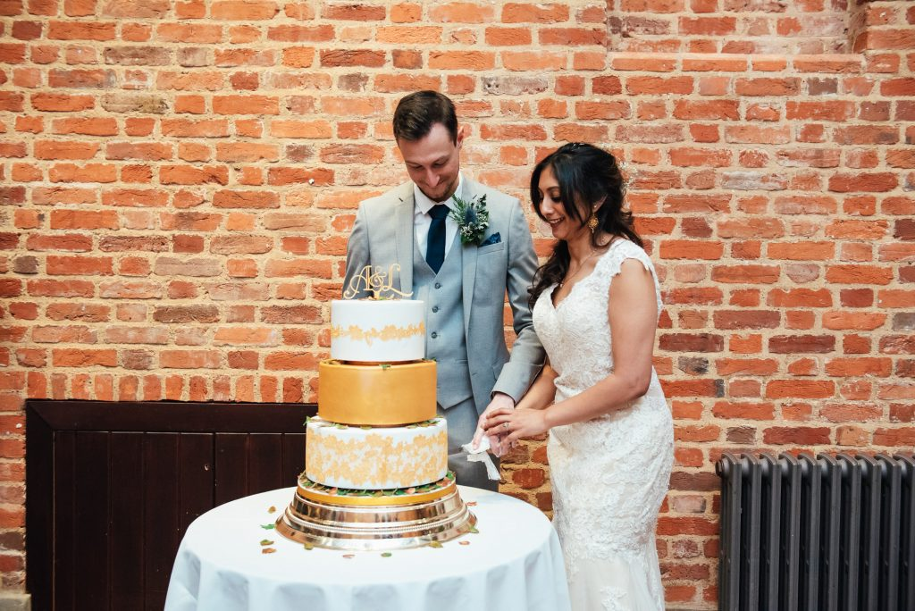 Couple cut the wedding cake at Forty Hall