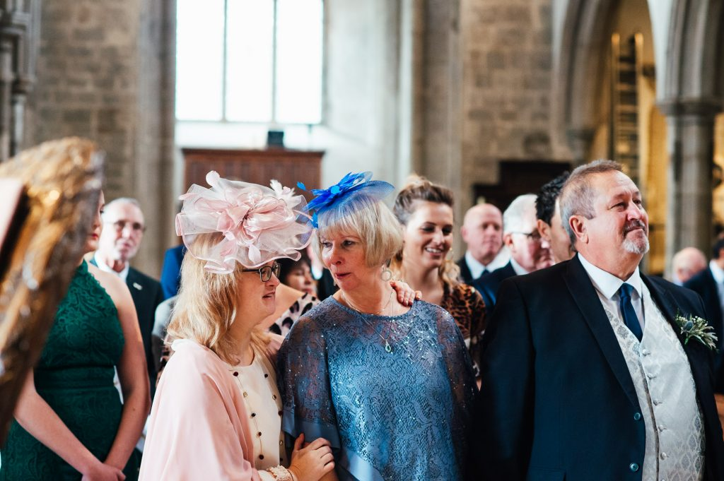 Candid moment between guests during London wedding ceremony