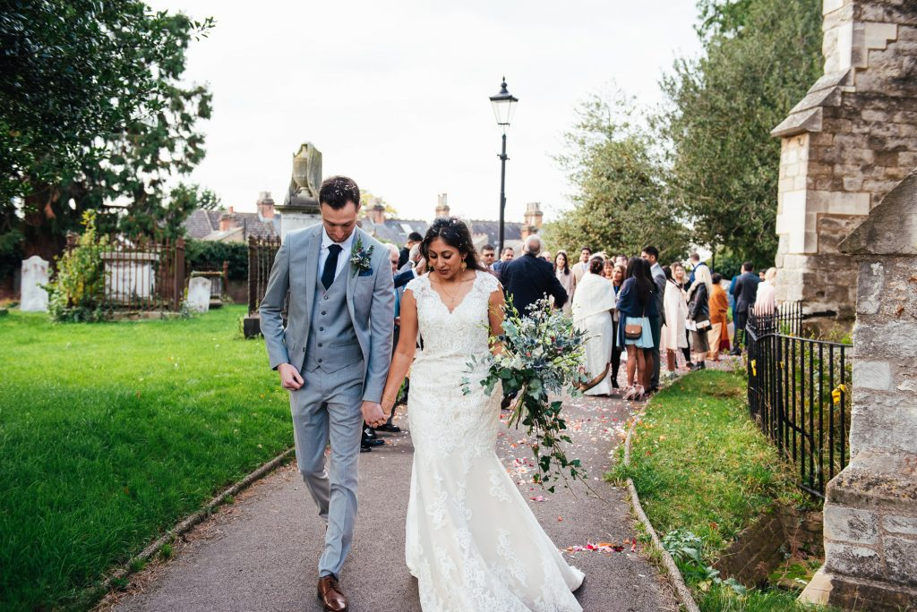 Couple walk together to their wedding car