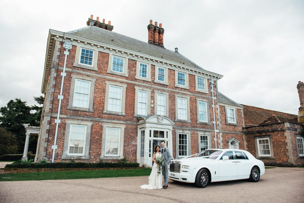Couple stand outside Forty Hall estate, a Rolls Royce car beside them