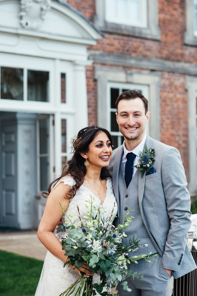 Groom in a charcoal grey three piece suit smiles at the camera with his bride laughing beside him