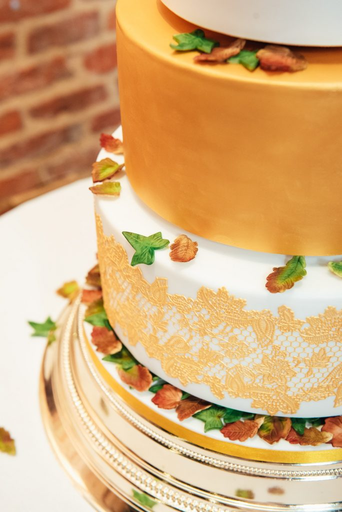 Three tier bespoke gold wedding cake with autumnal flower detailing