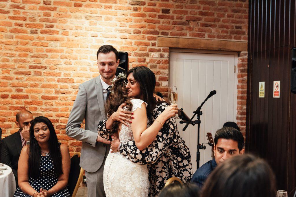 Emotional hug between bride and her maid of honour