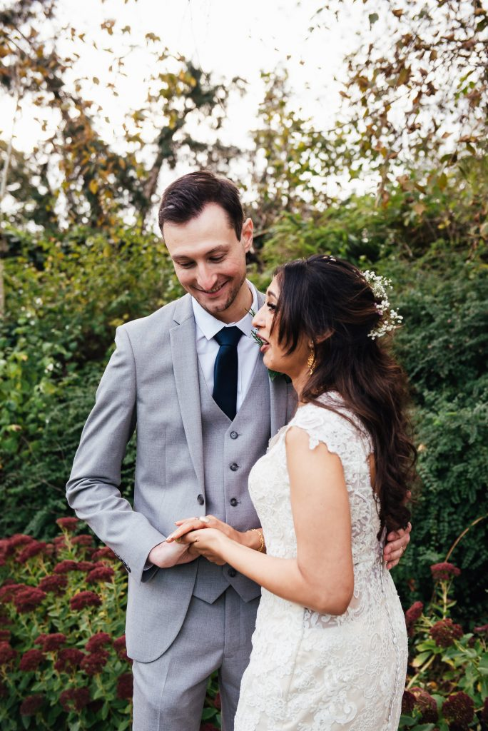 Handsome groom smiles with wife in outdoor couples portrait