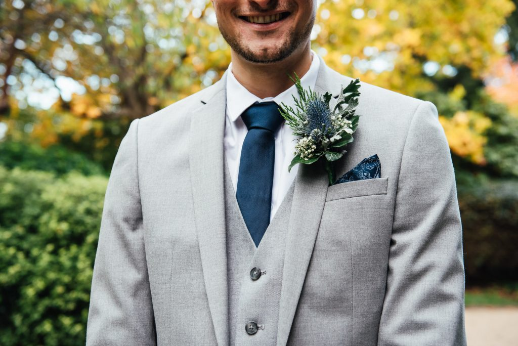Handsome groom in charcoal grey suit with navy blue tie