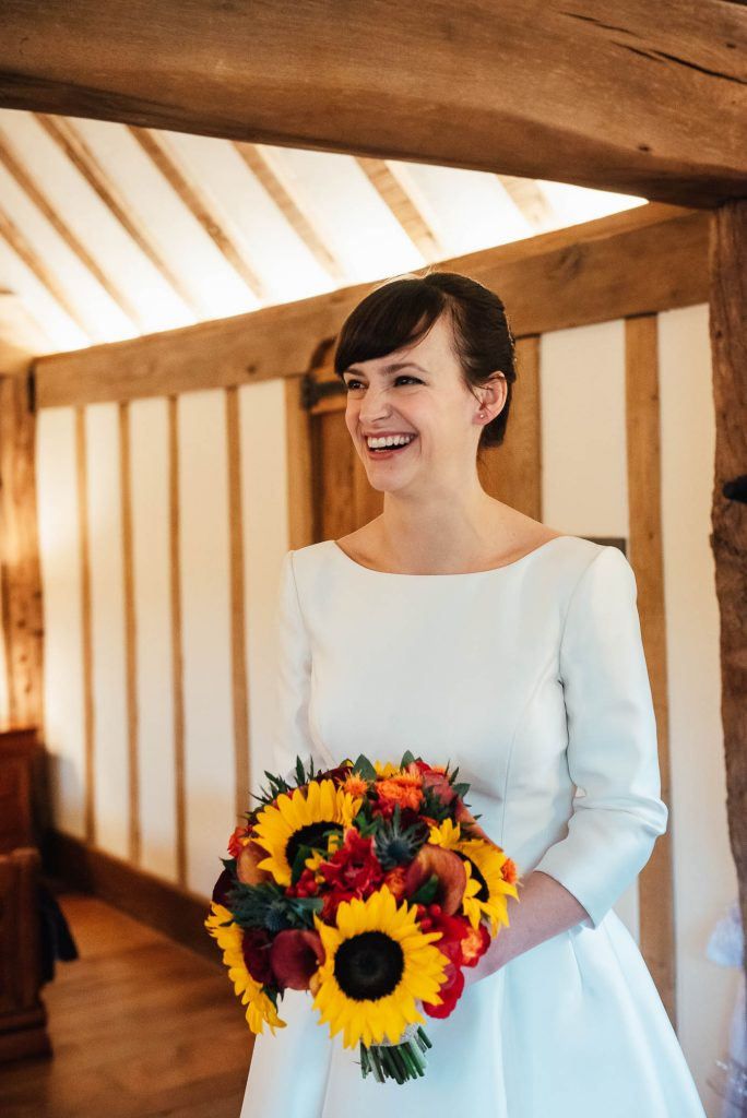 Beautiful bride holds Sunflower bouquet for autumn Cain Manor wedding