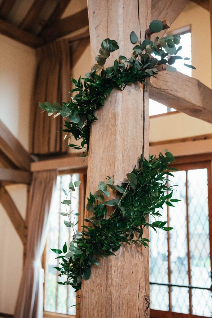 Fresh green florals wrapped around wooden posts