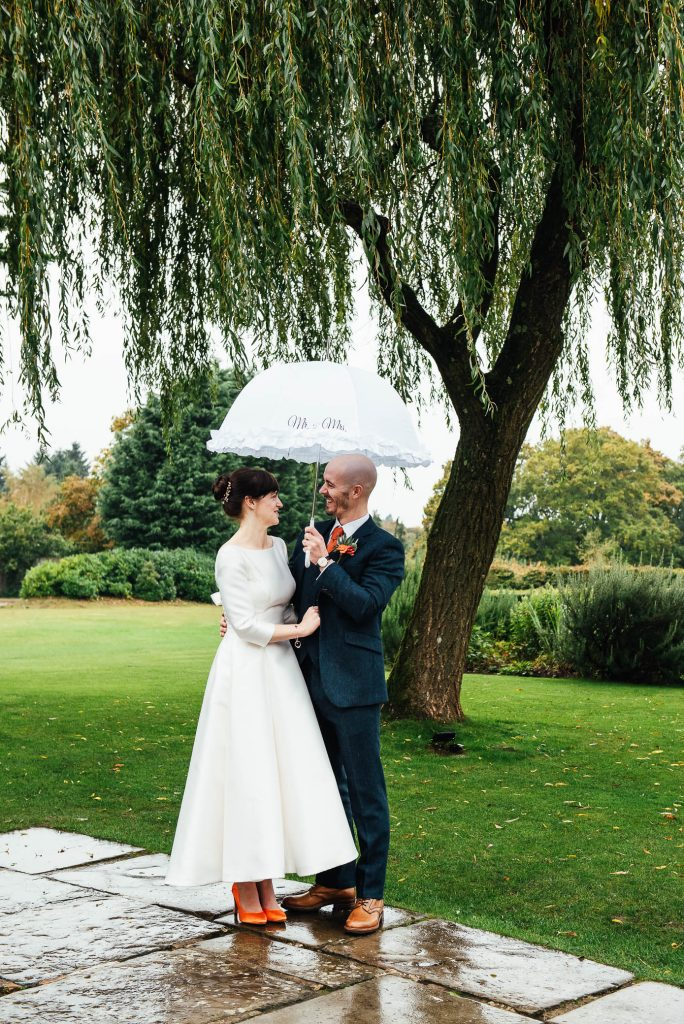 Couple laugh together as they shelter underneath white umbrella, Cain Manor wedding photography