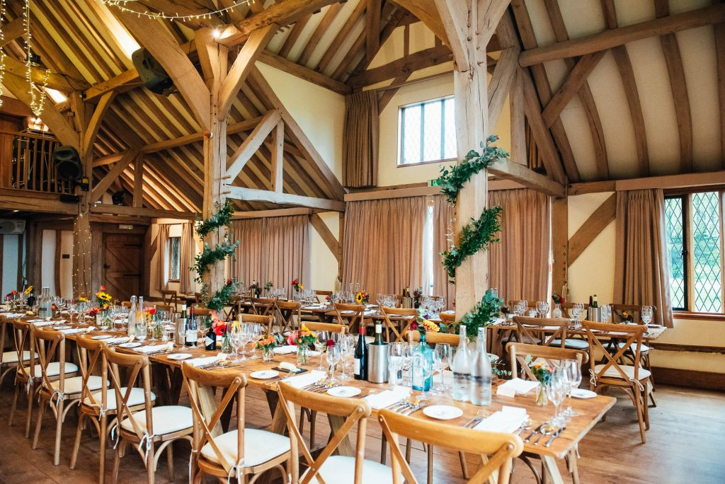 Cain Manor wedding breakfast room decorated with green foliage and candles