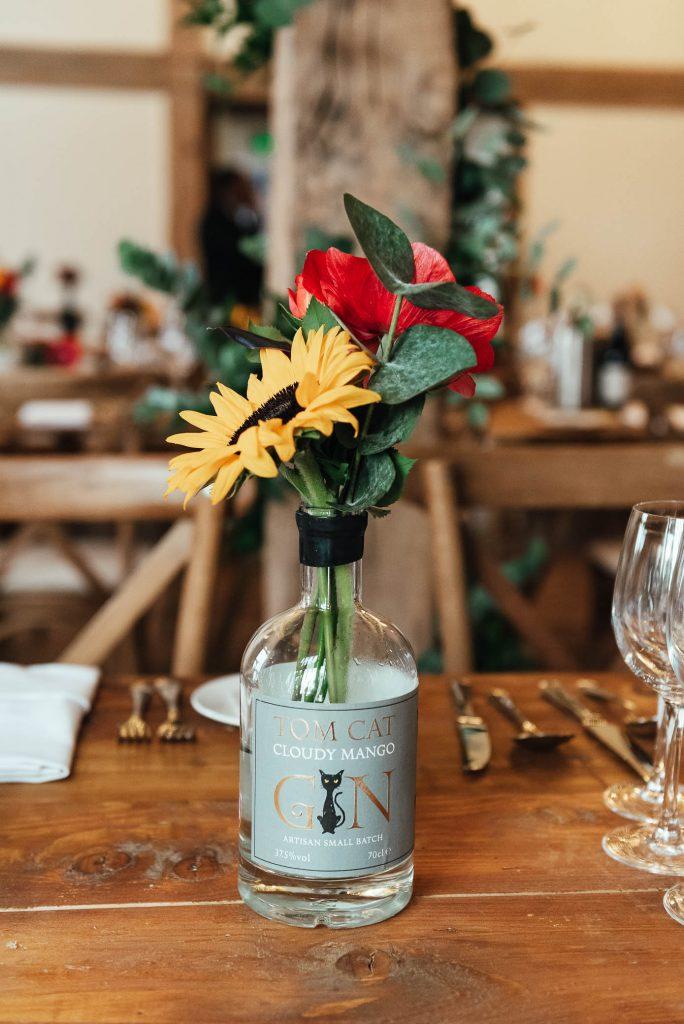 Bespoke wedding floral arrangement in classic gin bottle vase