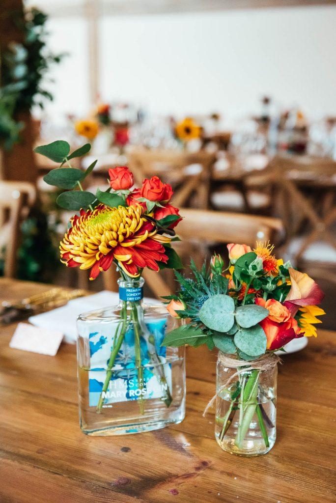 Bespoke wedding floral arrangement in classic gin bottle vases
