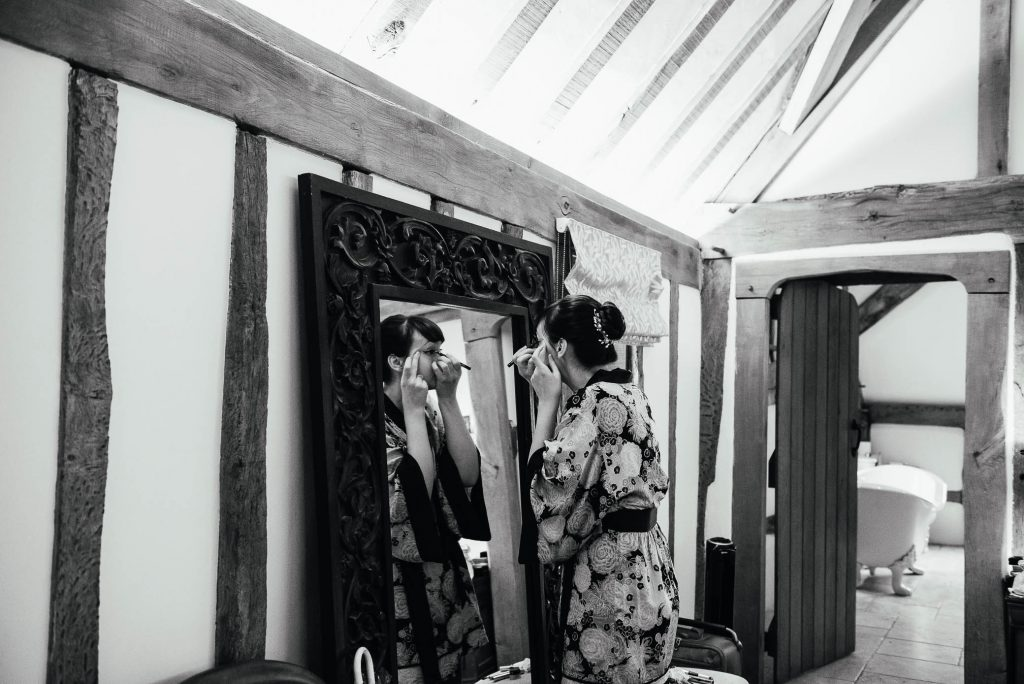 Black and white image of bride putting on her make up