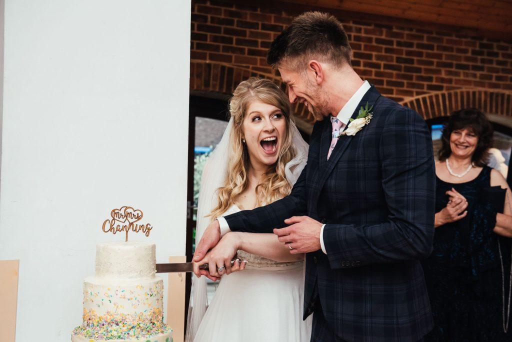 Bride and groom cut the wedding cake together Denbies Wine Estate Wedding