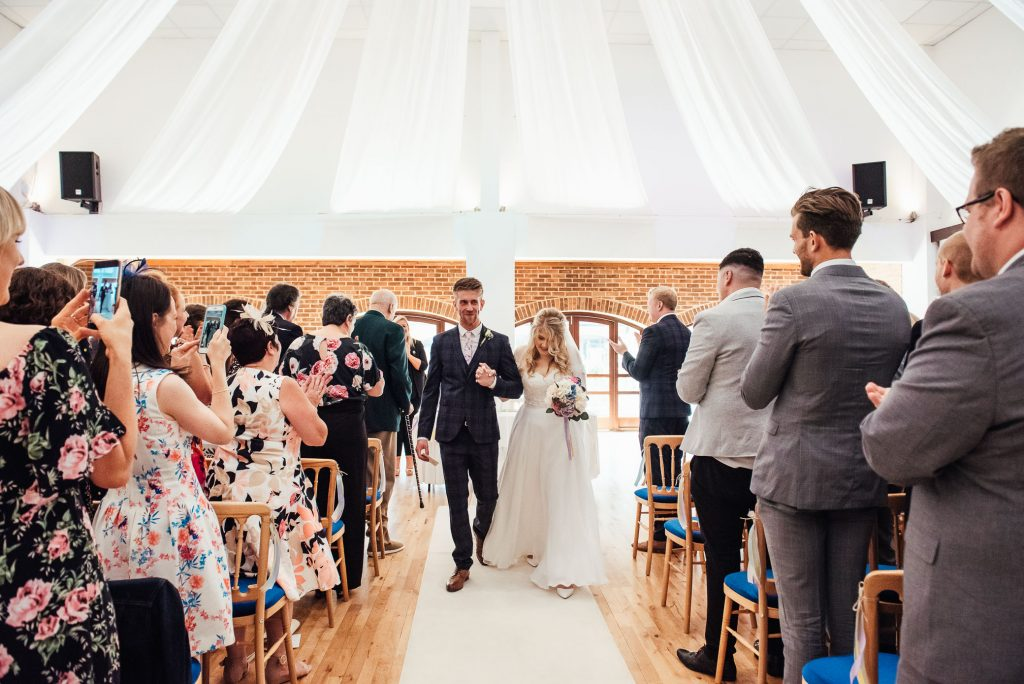 Newlywed couple walk back down the aisle together