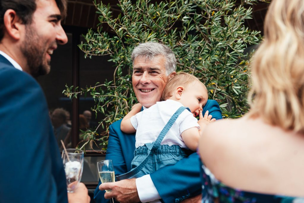Grandfather and grandson share a cuddle during the wedding reception
