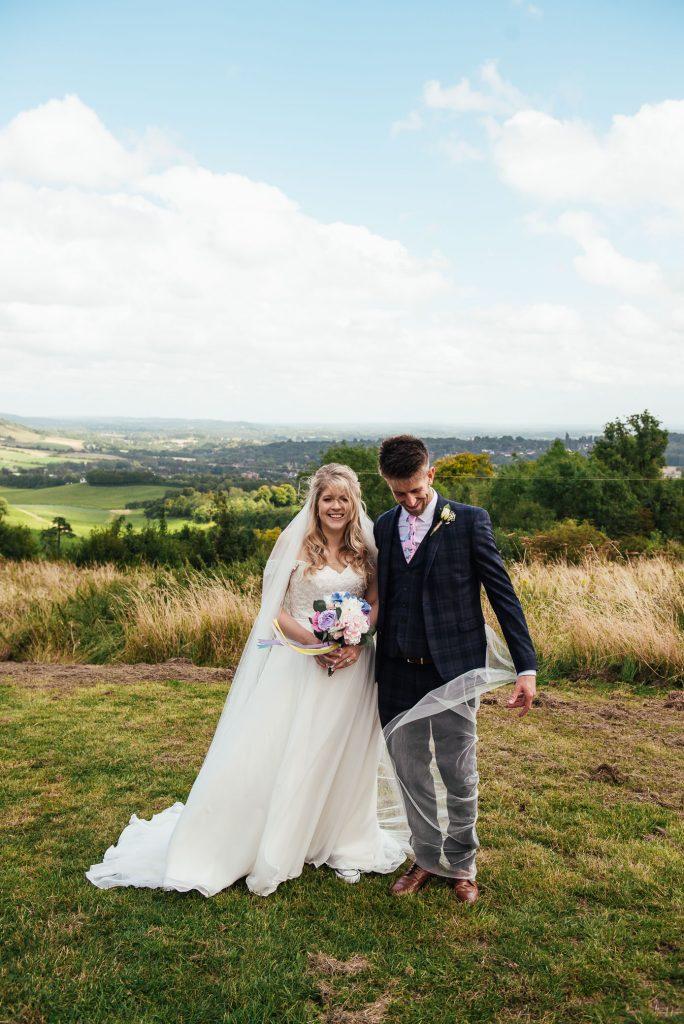 A windy couples portrait at the top of Denbies Wine Estate