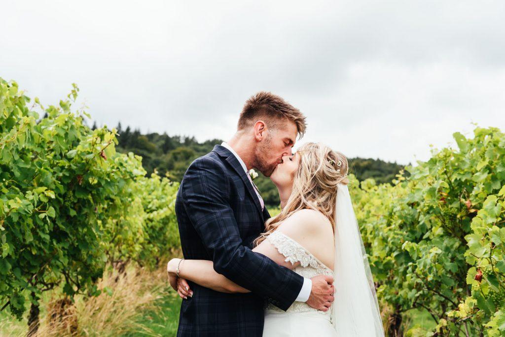 Couple kiss amongst the Surrey vineyards