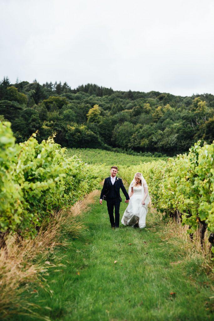 Newlywed couple walk down the grape vines