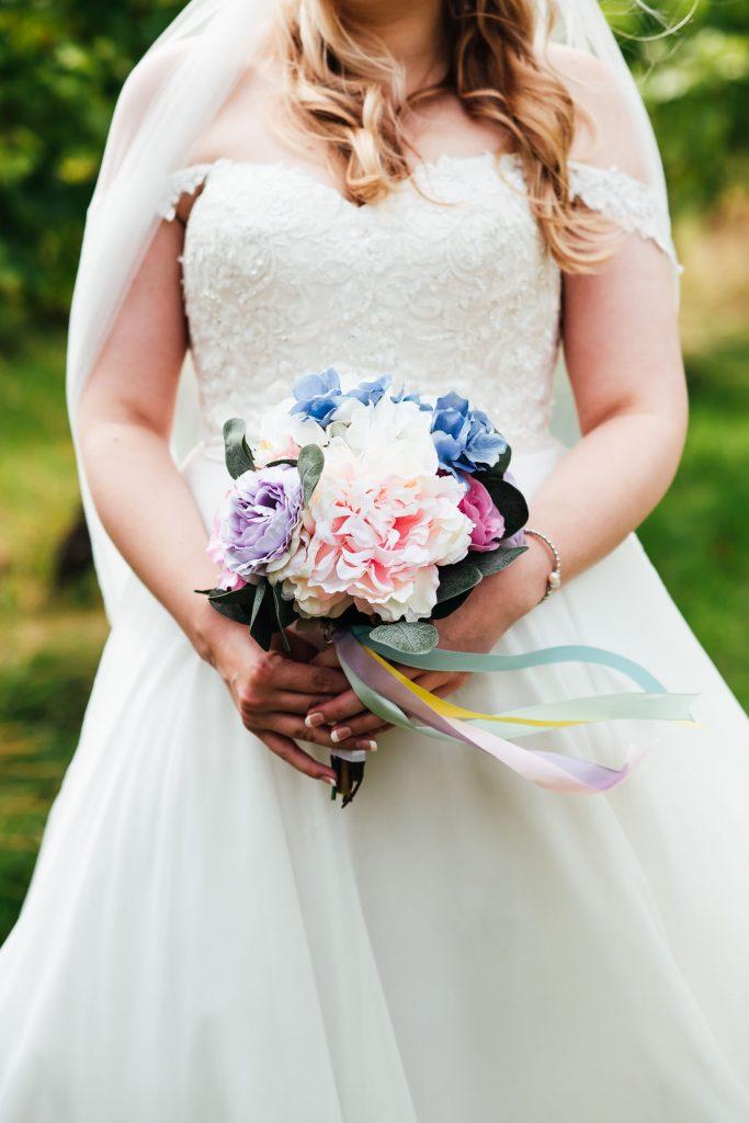 Natural bridal portrait, bride holds handmade coloured paper flower bouquet