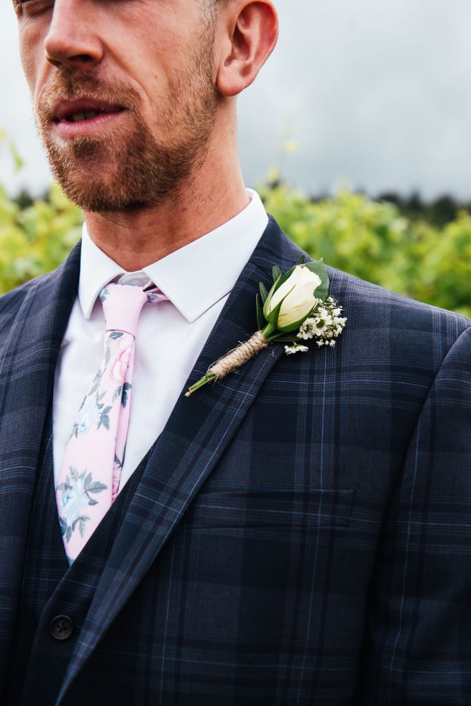 Handsome groom in a tailored navy blue three piece suit with chic white button hole