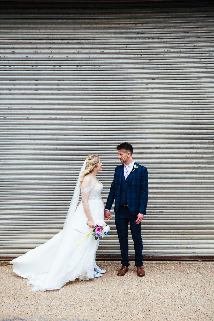 Artistic wedding portrait with couple in front of garage door