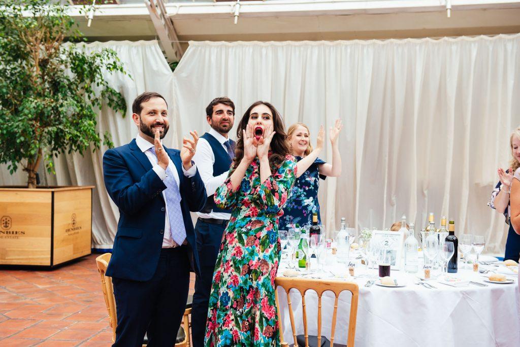Wedding guests cheer as bride and groom enter wedding breakfast room