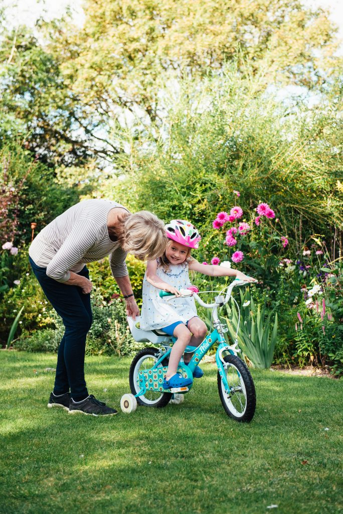 Grandmother helps granddaughter cycle her bike